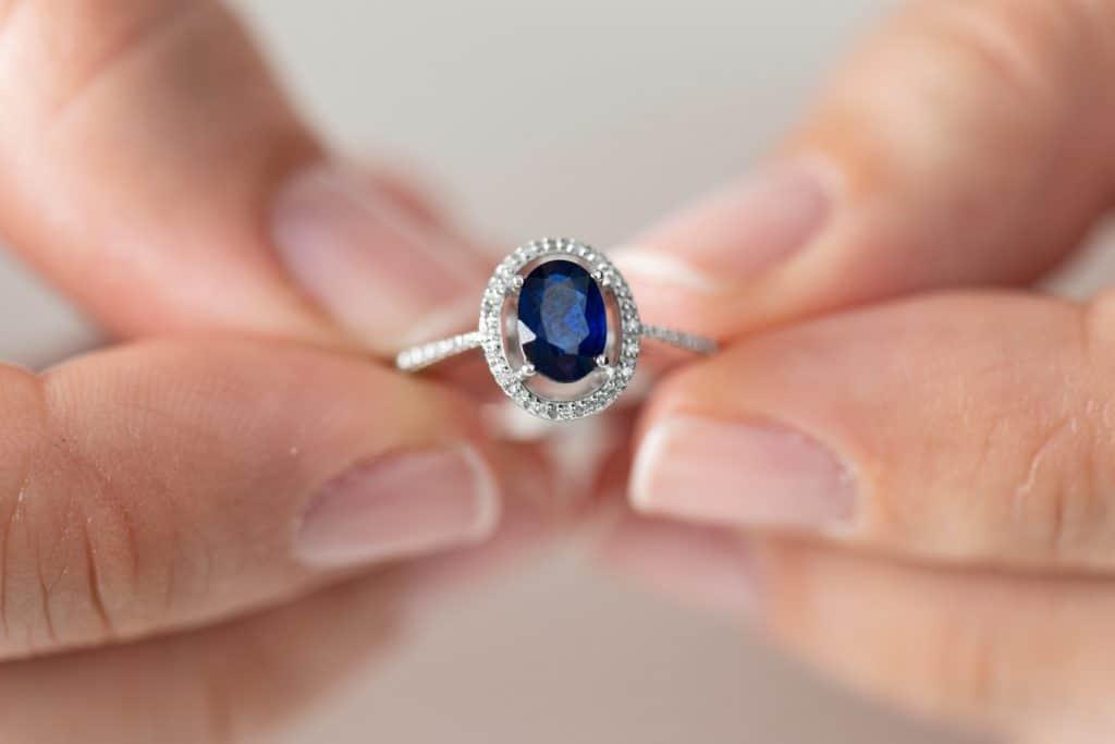 Hands holding diamond ring. Sapphire.