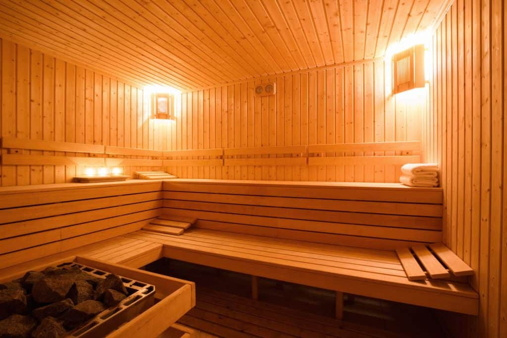 Interior of a modern rustic sauna room with wall lights