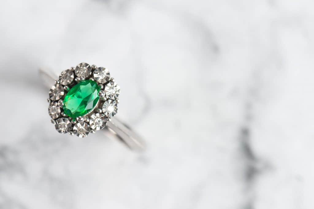 Luxury emerald ring on marble background.