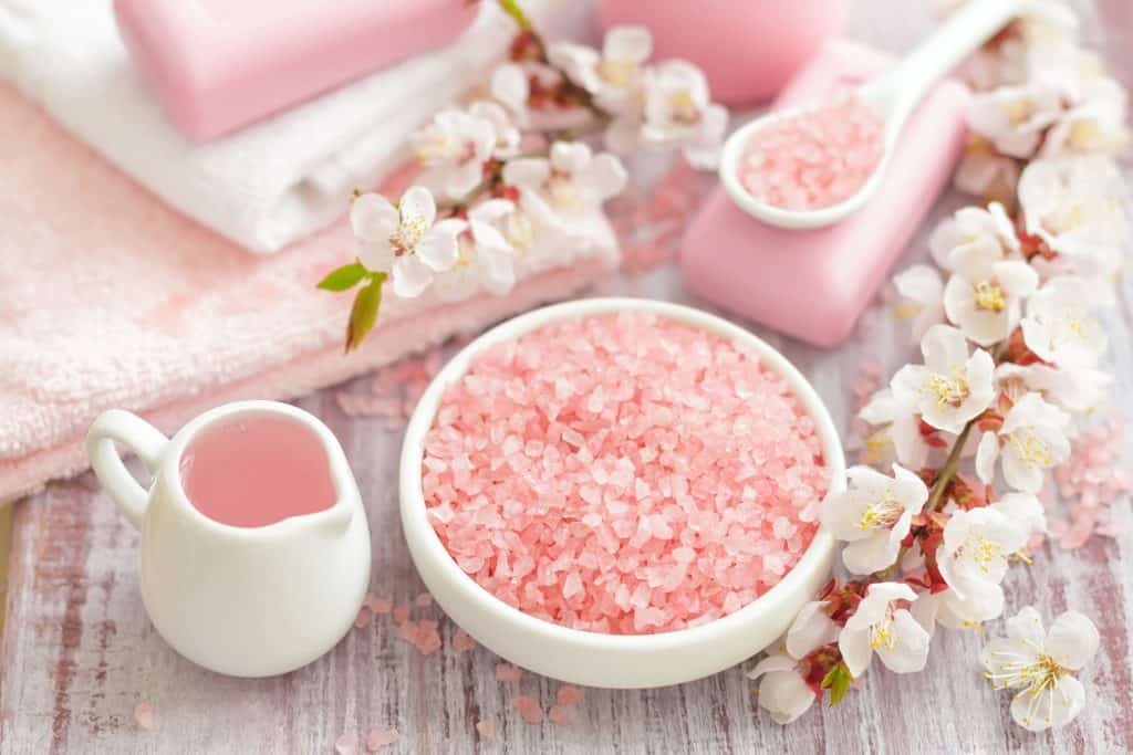 Pink sea salt on white containers with decorative flowers on the sides