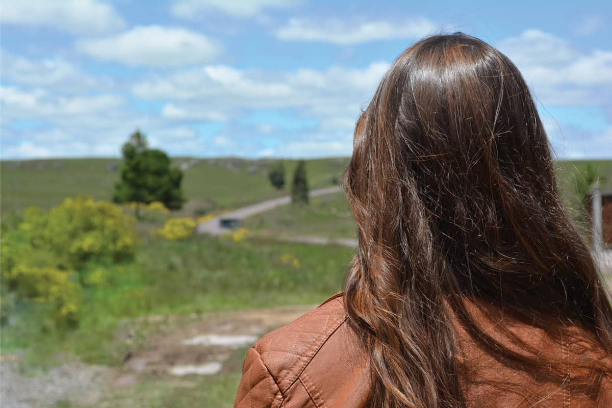 Rear view of a woman from back, with a natural long loose hair, wearing a brown faux leather jacket looking at landscape with grass and a curved road.