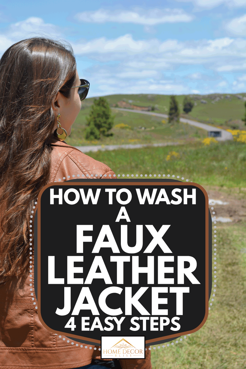 Rear view of a woman from back, with a natural long loose hair, wearing a brown synthetic leather jacket looking at landscape with grass and a curved road. How To Wash A Faux Leather Jacket [4 Easy Steps]