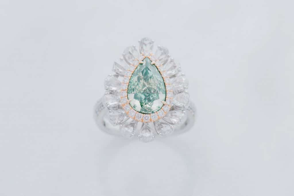 Ring with diamonds and turquoise diamond on white background.