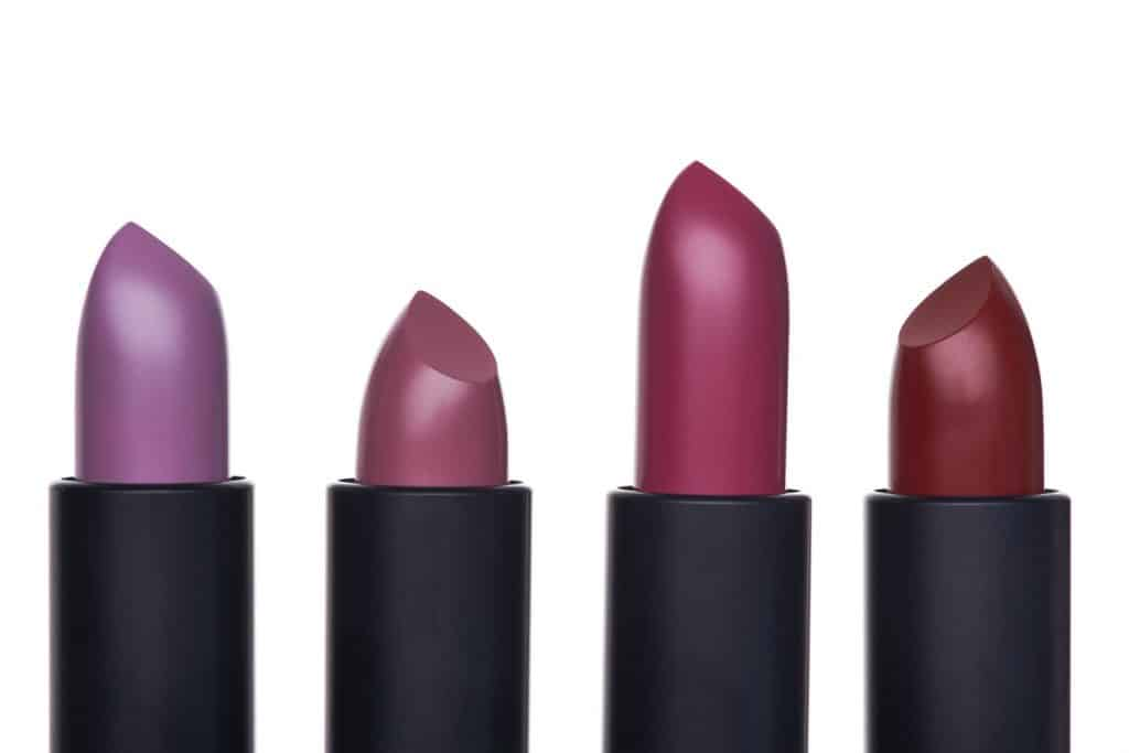 Rolled up different colored lipsticks on a white background
