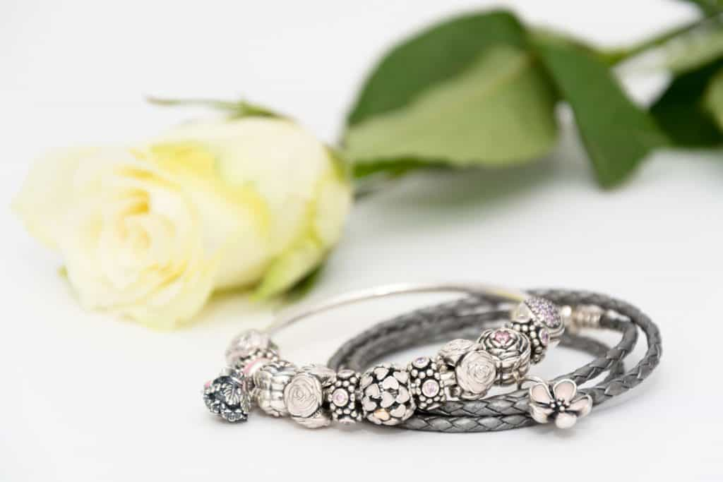 Two beautiful Pandora bracelets combined of different charms (beams) on white background next to a beautiful rose, How Many Charms Fit On A Pandora Bracelet? [By Type Of Bracelet]