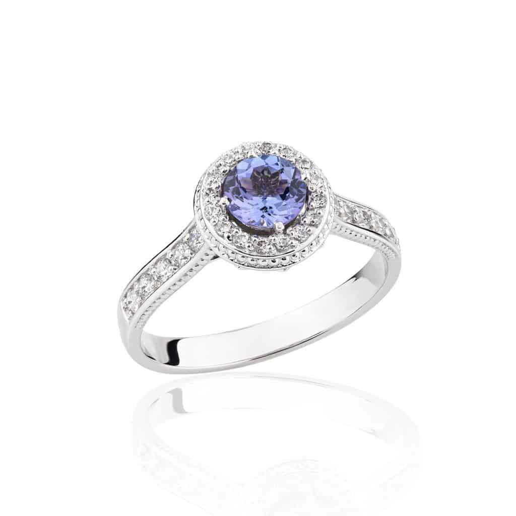 Wedding diamond ring isolated on a white background. Silver engagement ring with blue gemstone Tanzanite