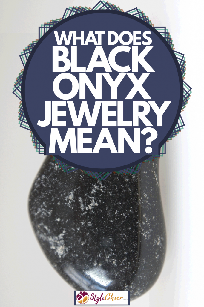 An up close photo of a black onyx stone on a pale gray background, What Does Black Onyx Jewelry Mean?