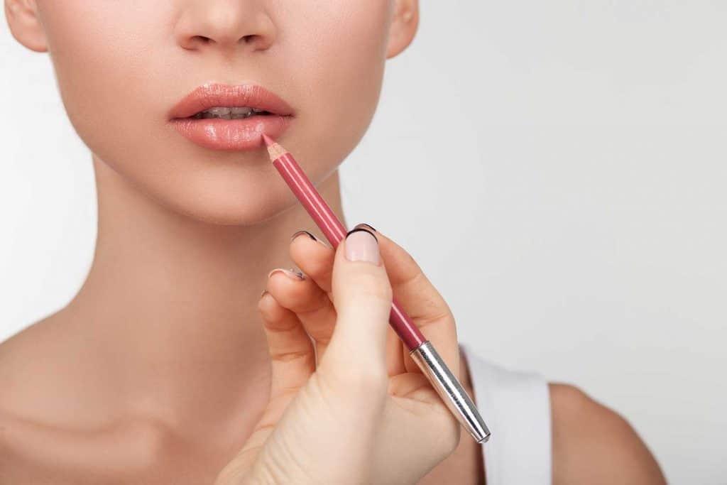 Young woman applying lip liner makeup