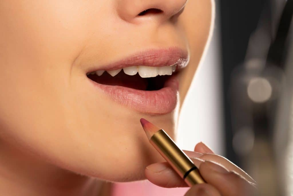 Young woman applying lip liner on her lips on white background, Do Lip Liners Ever Expire?