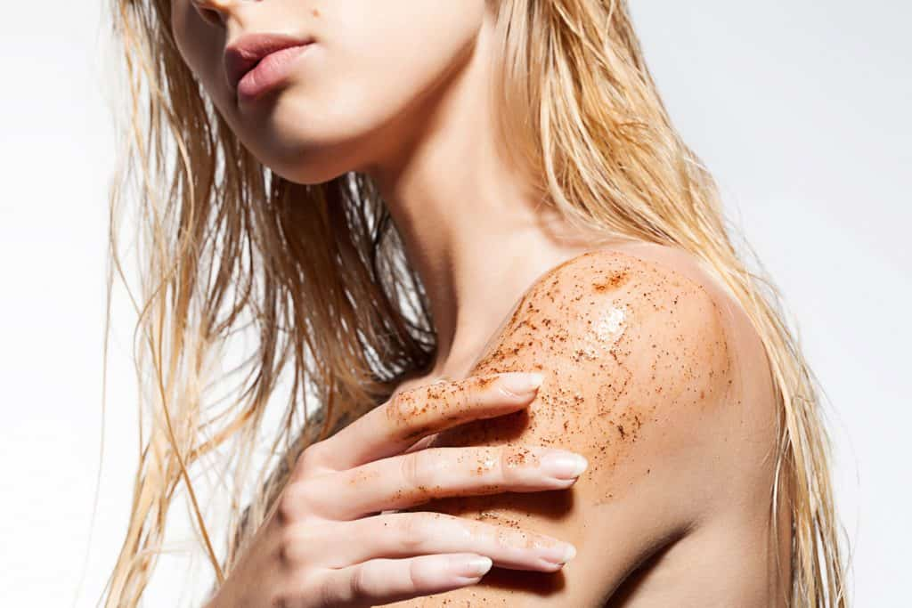 A blonde woman putting on body scrub on her shoulder while in the shower, 10 Types Of Body Scrubs And Their Ingredients