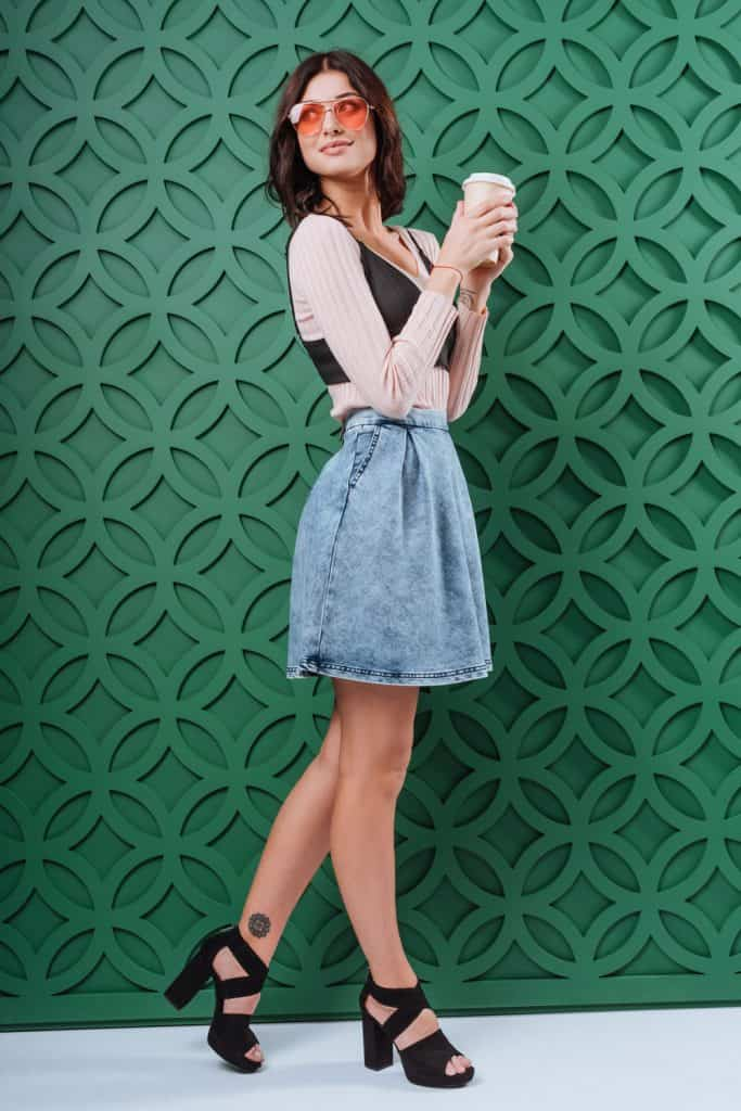 A tall and beautiful woman wearing a denim skirt on a green background