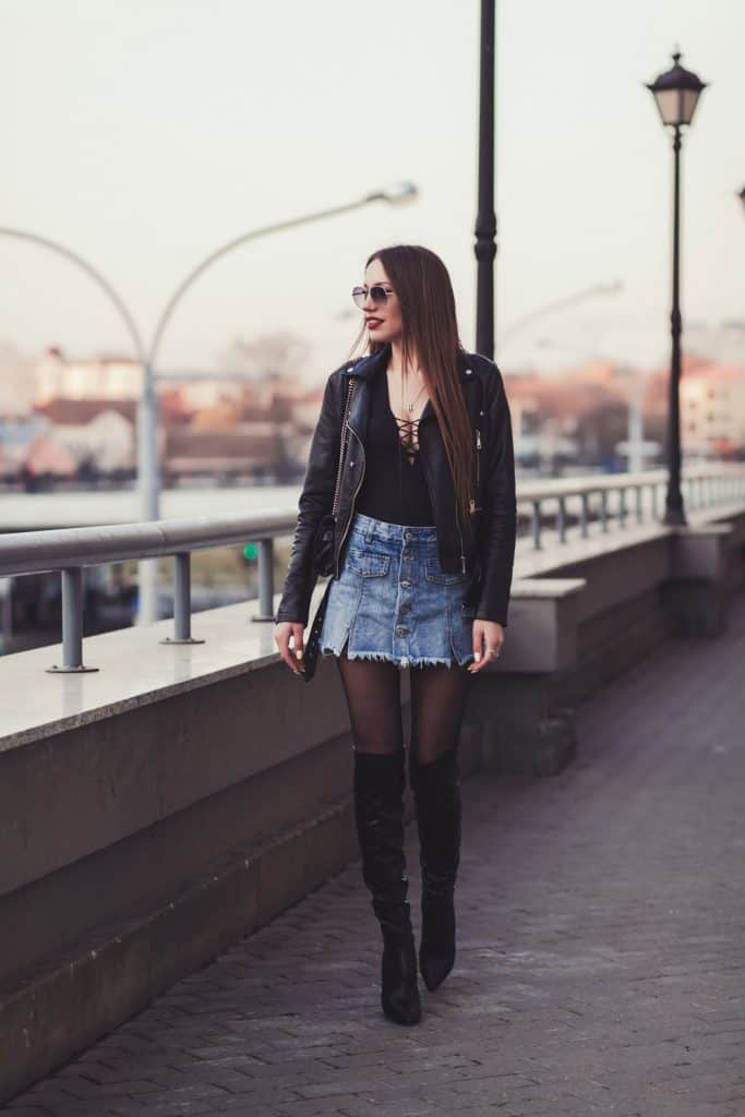 A tall sexy woman a denim jacket, denim skirt, and black stockings matching her boots