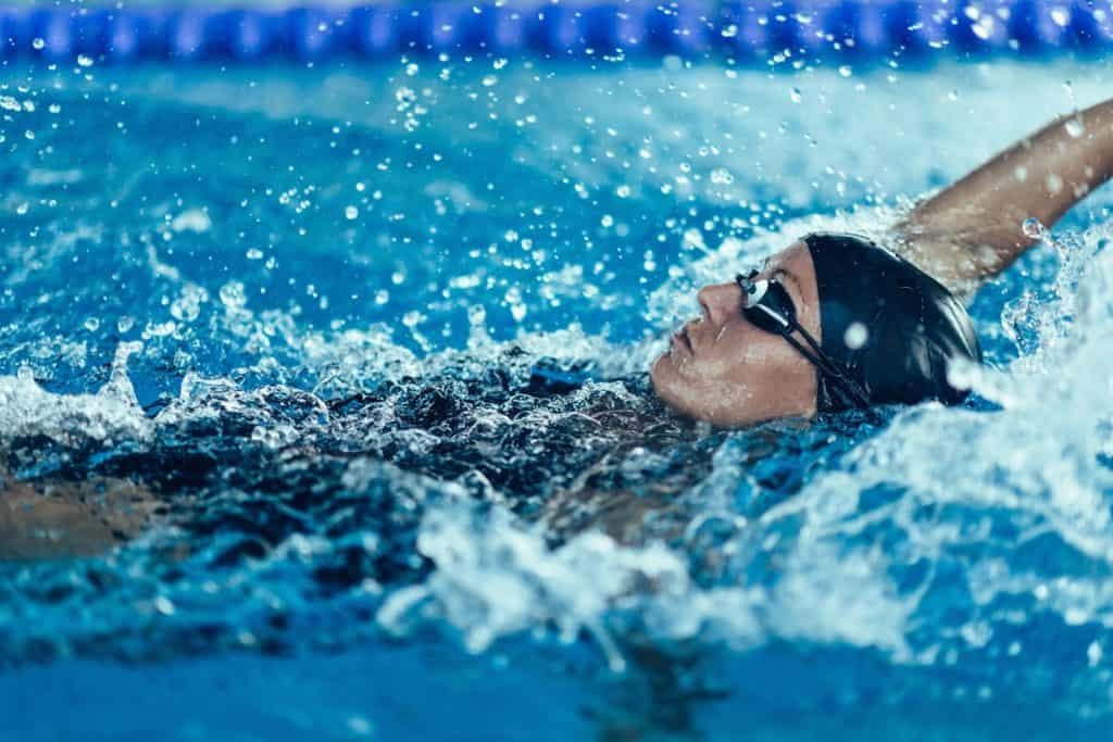 A woman doing a backstroke on an Olympic swimming pool
