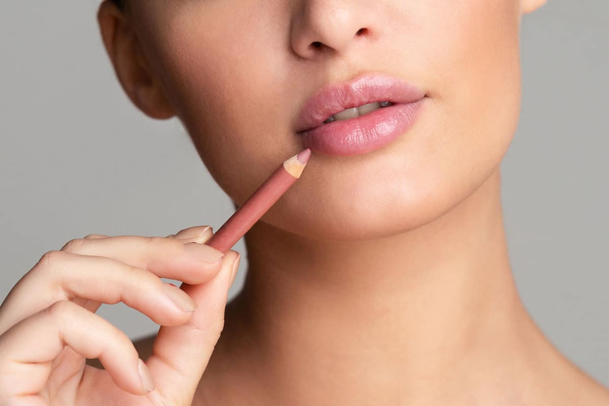 A woman drawing her lips on a pink nude lipstick