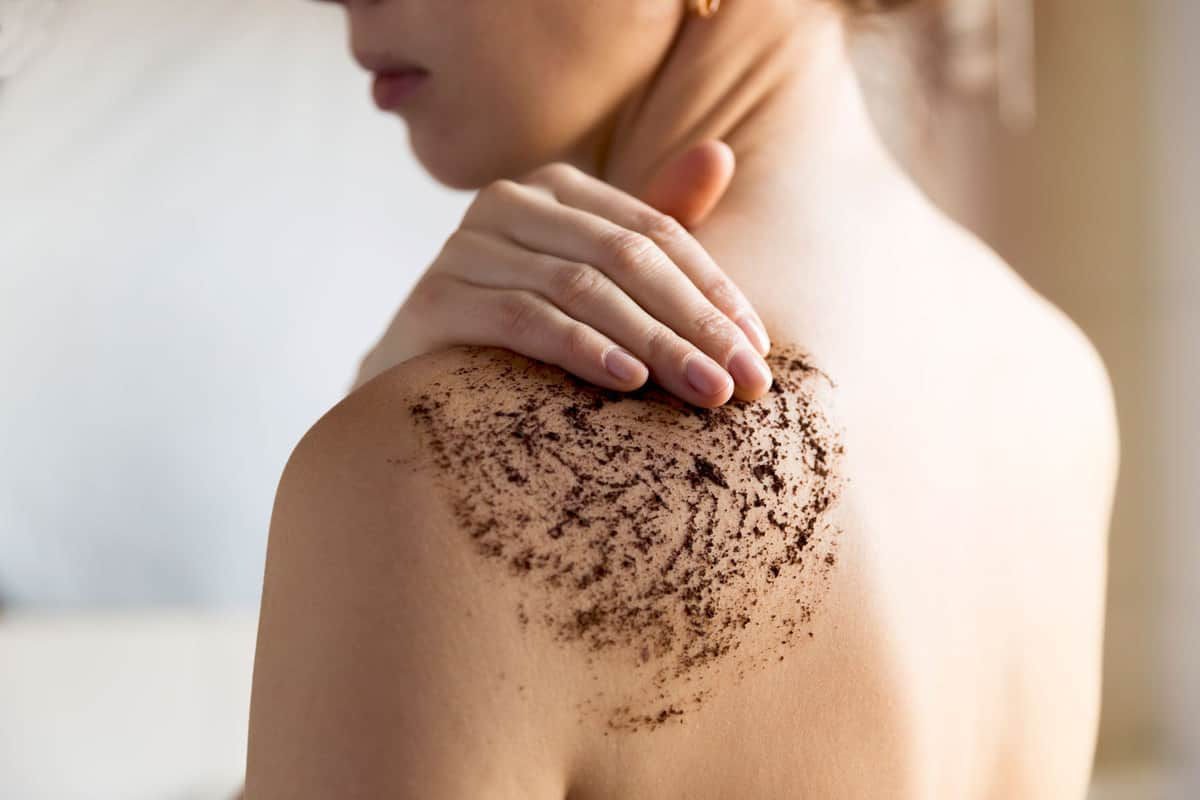 A woman putting on body scrub on her back, 10 Types Of Body Scrubs And Their Ingredients