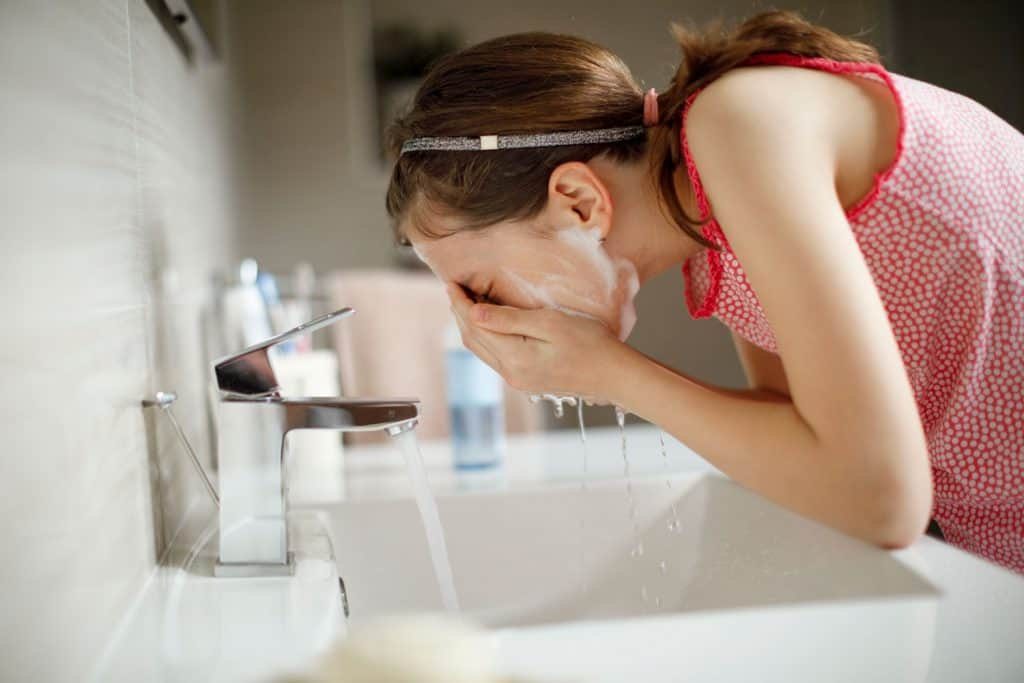 A woman washing her face with face wash, How Long Does Face Wash Last?