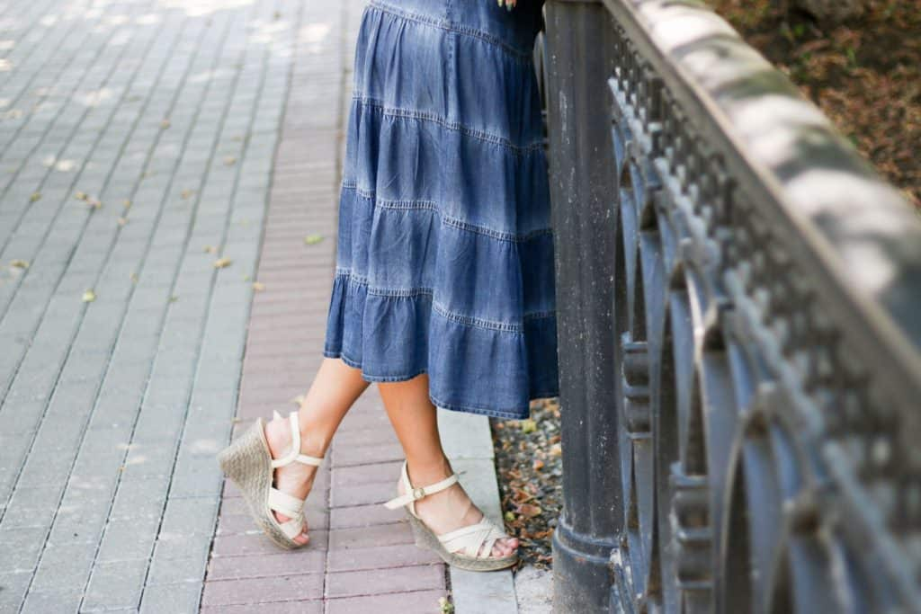 A woman wearing wedge high heels and a long denim skirt