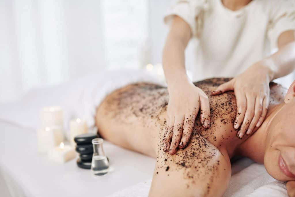 Beautifican massaging back of male client with coffee scrub and essential oil