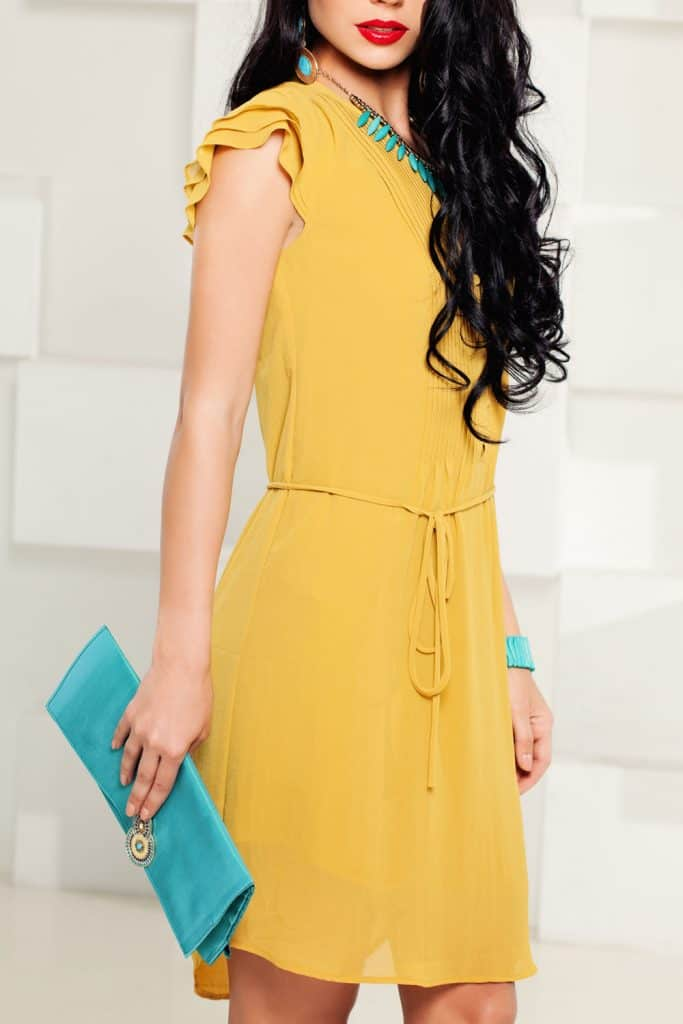 Beautiful Fashion Model Girl wearing mustard dress and holding a Turquoise purse and jewelries