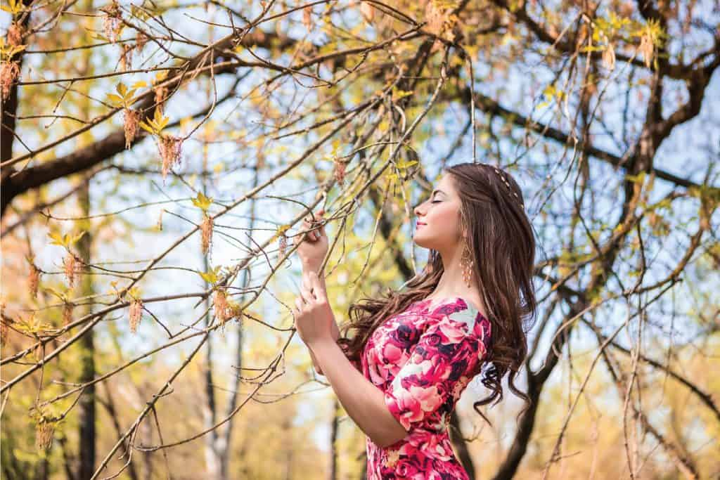 Beautiful girl holding branches of trees. Young woman in a forest park wearing bodycon dress. 6 Of The Best Shoes To Wear With A Bodycon Dress