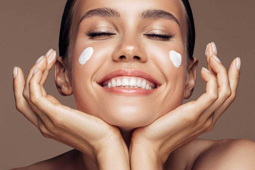 Beautiful woman applying cream on her face, 10 Best Night Creams With Hyaluronic Acid