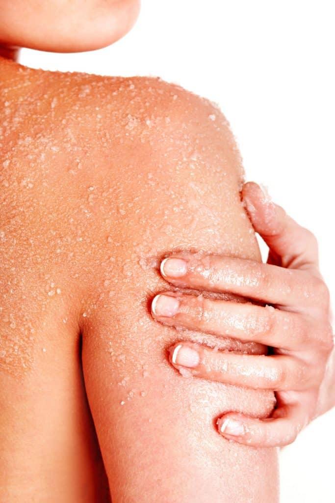 Beautiful young woman scrubbing body