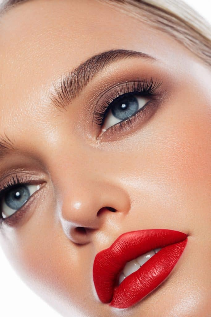 Close-up portrait of young woman with red lipstick
