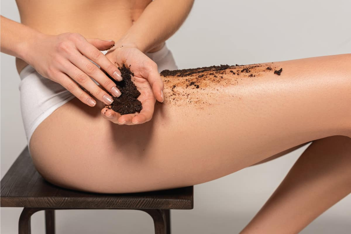 Cropped view of woman applying coffee exfoliant while sitting on chair