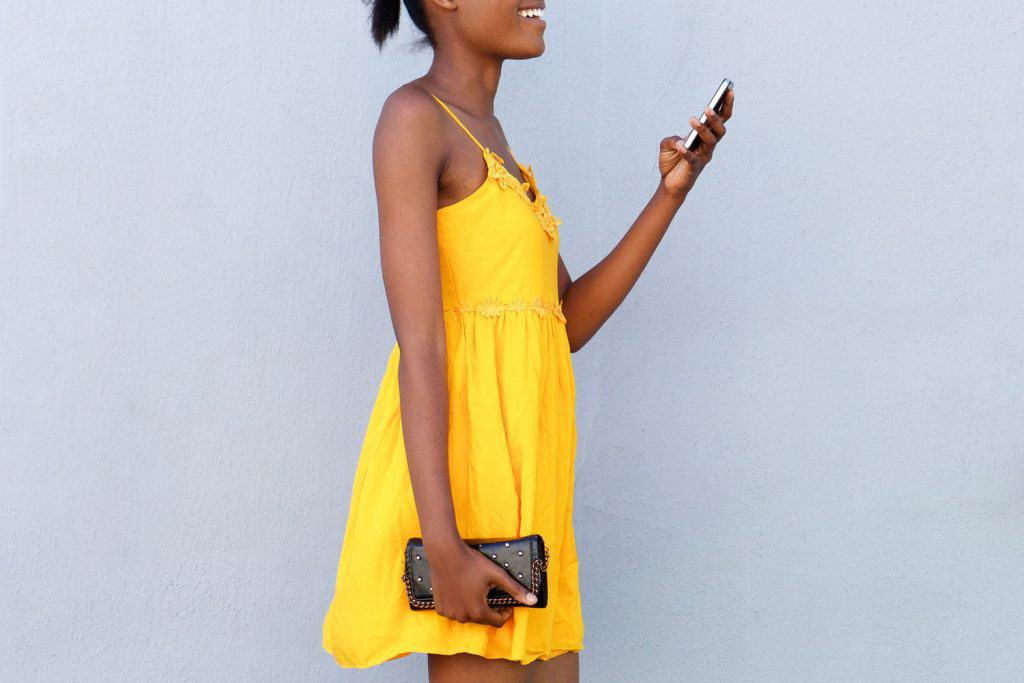 Full length side portrait of attractive african woman walking reading text message on mobile phone wearing mustard dress