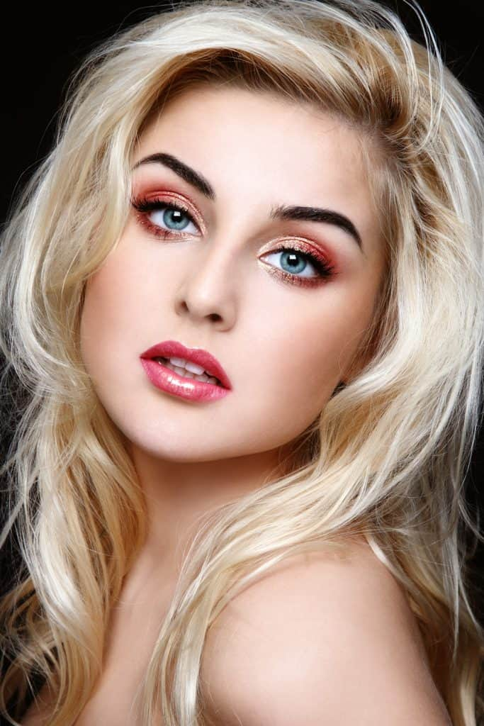 Girl with blonde hair and blue eyes with bold color makeup