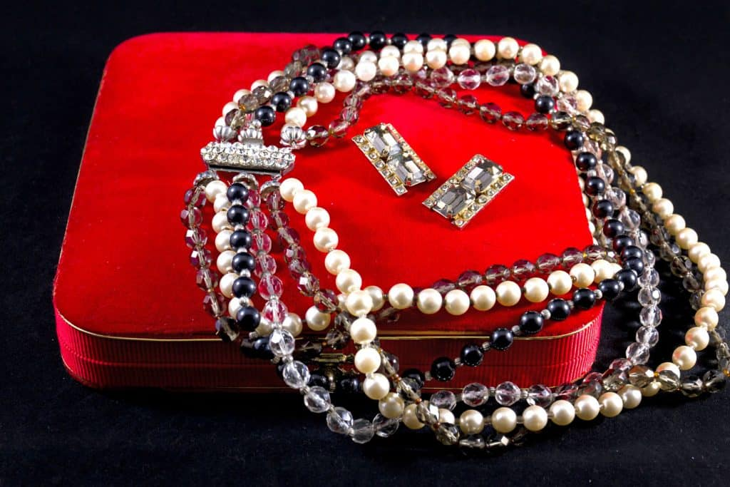 Gorgeous and luxurious pearl necklaces on a red pillow, 5 Ways To Keep Necklaces From Tangling On Your Neck