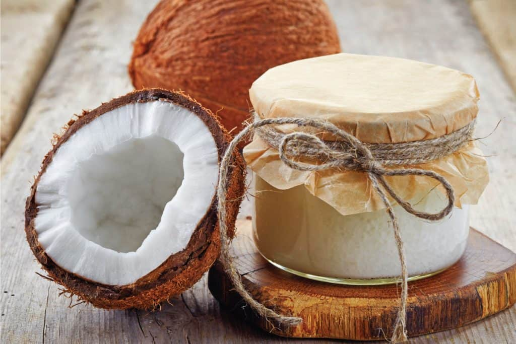 Jar of coconut oil and fresh coconuts. How To Make Body Scrub With Coconut Oil [Including 5 Effective Recipes]