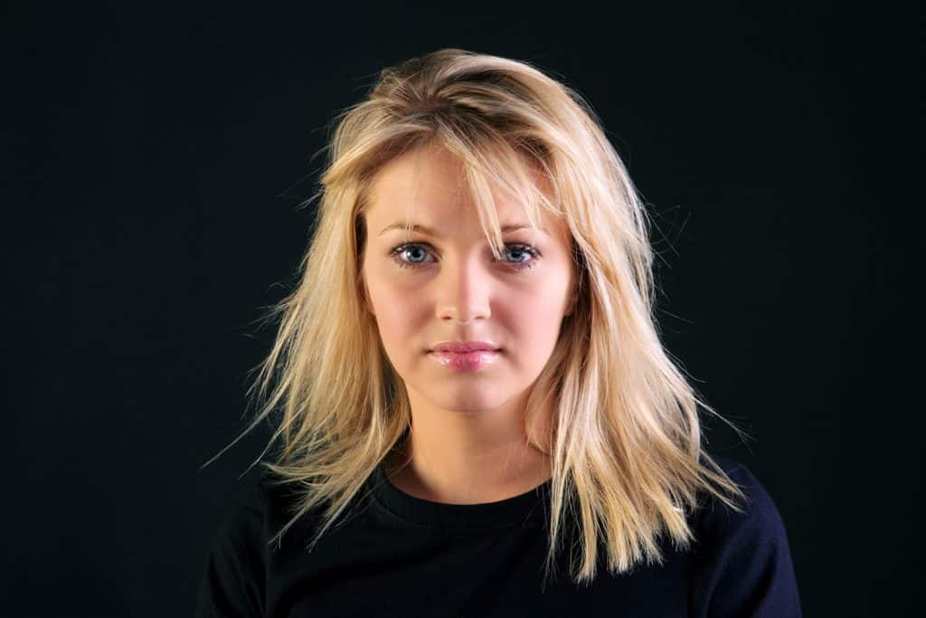 Portrait of a beautiful blonde haired woman with blue eyes on a black background.