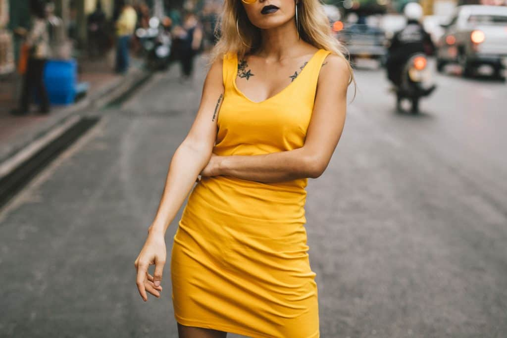 Portrait of fashionable Asian woman in the streets of bangkok. She's wearing a yellow dress and is looking at the camera