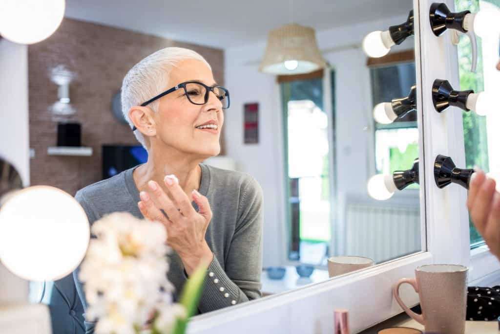 Portrait of senior woman with short grey hair looking at herself in the mirror and applying face cream, 25 Makeup Ideas For Women Over 50 With Gray Hair