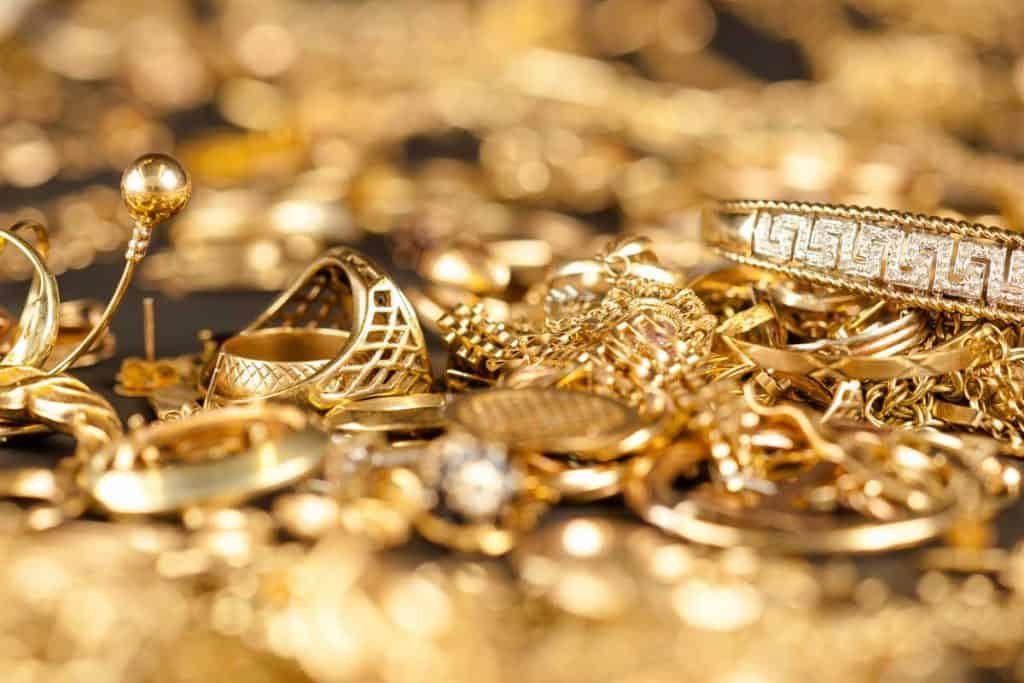 Table of scrap gold being inspected, What Does 18k Gold-Plated Mean? [All You Need To Know!]
