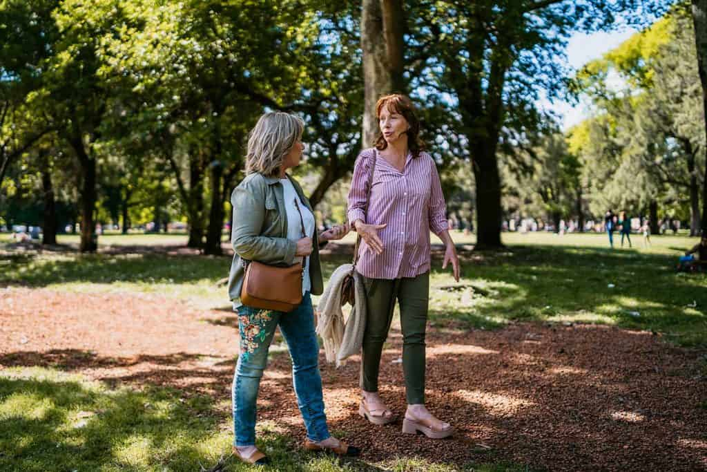 Two senior women walking outdoor together on a sunny day
