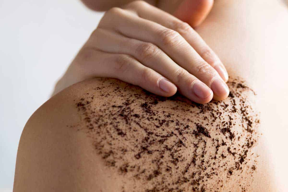 Woman cleans skin of the body with coffee scrub in bathroom, Does Body Scrub Expire? [And How To Tell If Yours Has!]