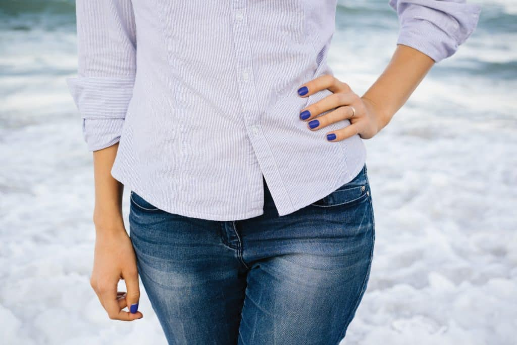 Woman in faded jeans and shirt standing in the sea foam on the beach. 4 Methods To Fade Jeans