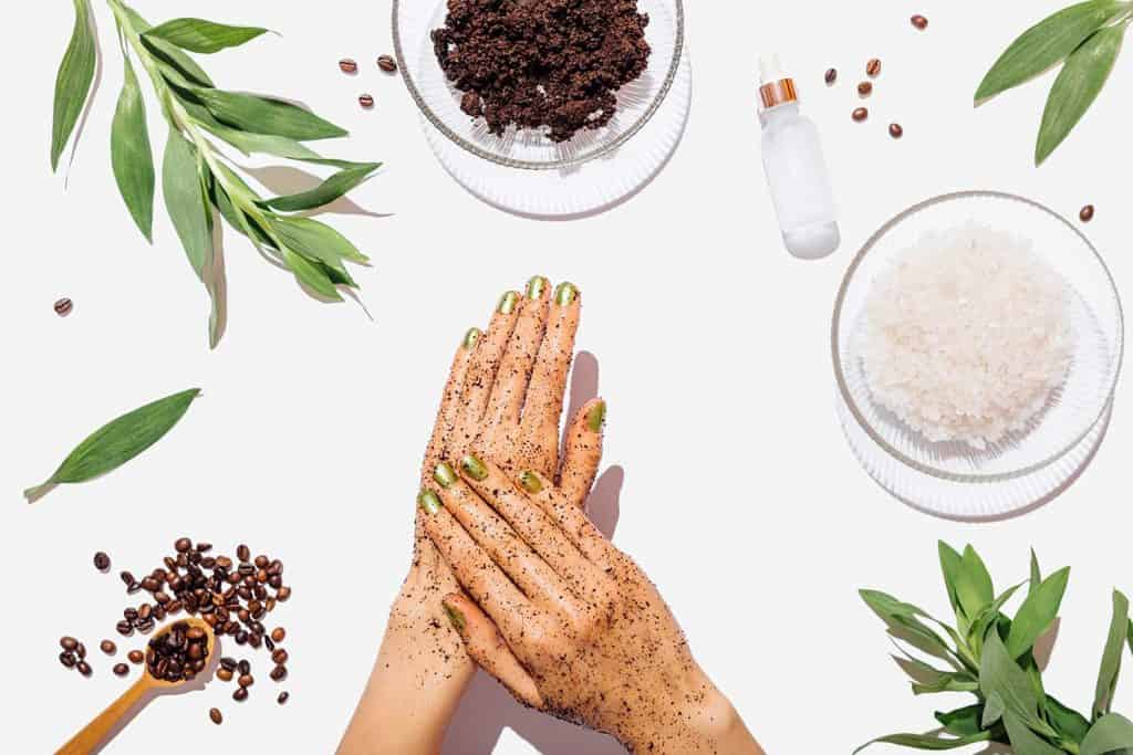 Woman's hands massaging natural homemade coffee scrub with coconut oil on white table next to ingredients