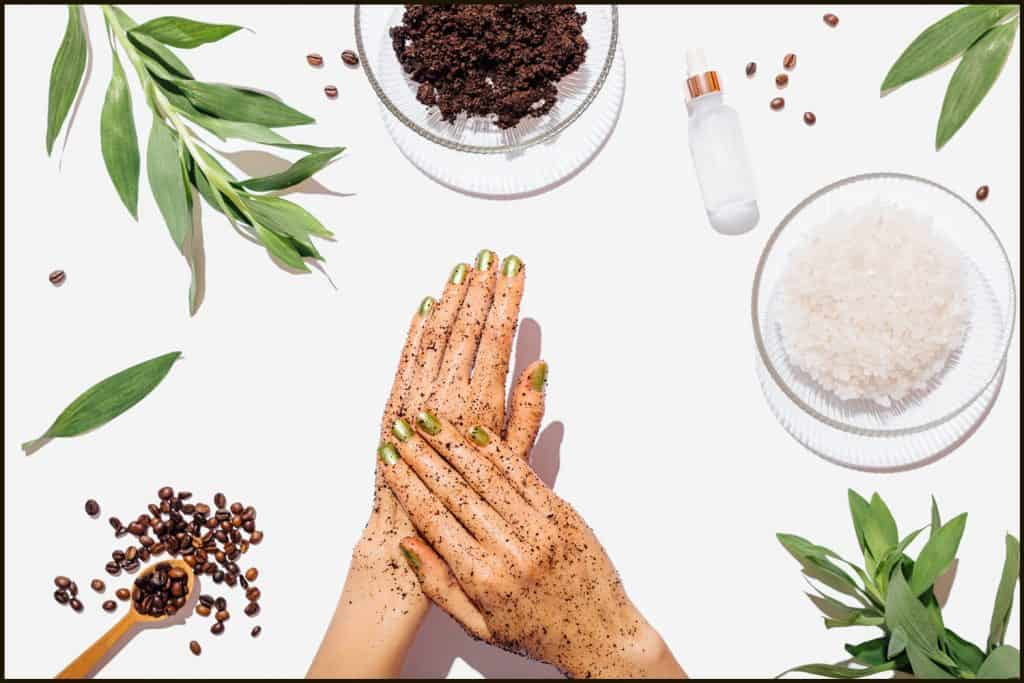 Woman's hands massaging natural homemade coffee scrub with coconut oil on white table next to ingredients, view from above, Does Body Scrub Remove Tan And Make Skin Lighter?