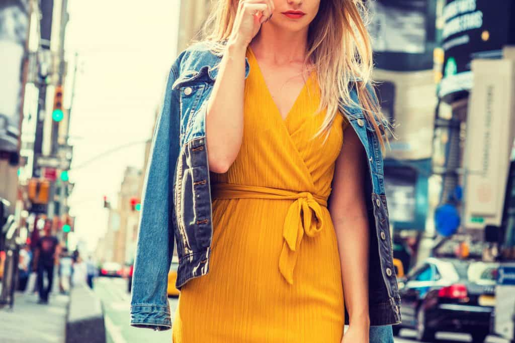 Young Eastern European Woman traveling in New York, with long brown hair, wearing yellow dress, blue Denim jacket draped over shoulder, blue sunglasses, walking on street in Times Square of Manhattan, 11 Awesome Mustard Dress Outfits [Summer And Winter Ideas!]