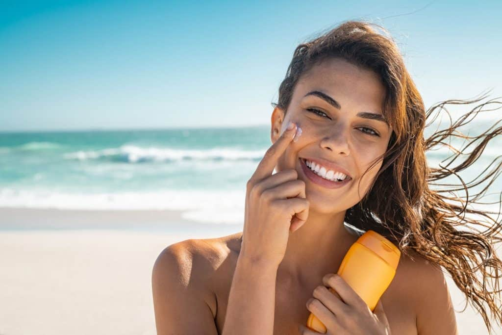 A beautiful woman putting sunscreen on her face at the beach, Can Sunscreen Replace Moisturizer? [And Vice Versa]