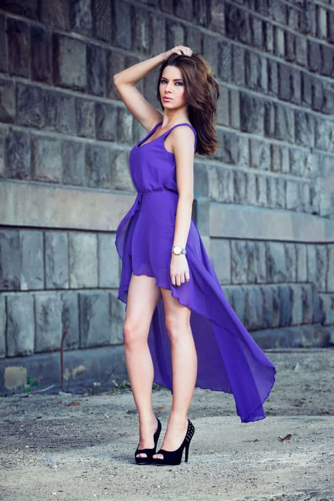 A beautiful woman wearing a purple dress and black shoes on a concrete background