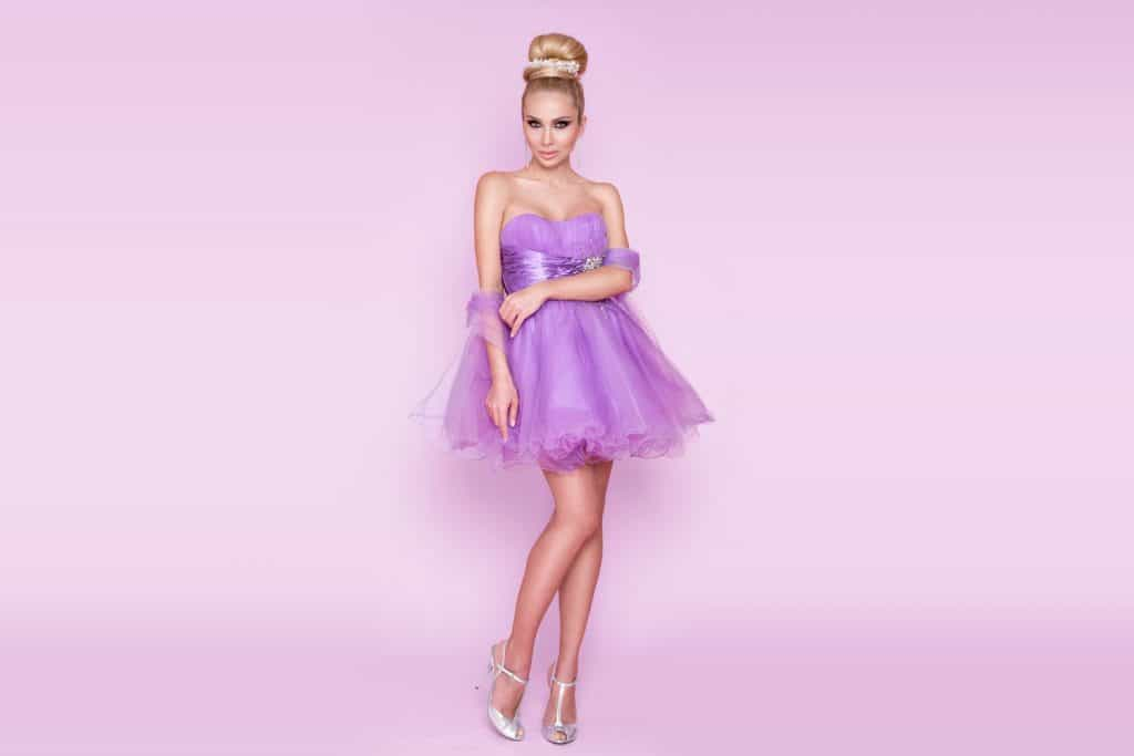 A beautiful woman wearing purple strapless dress on a purple background, What Color Lipstick Goes With A Purple Dress?