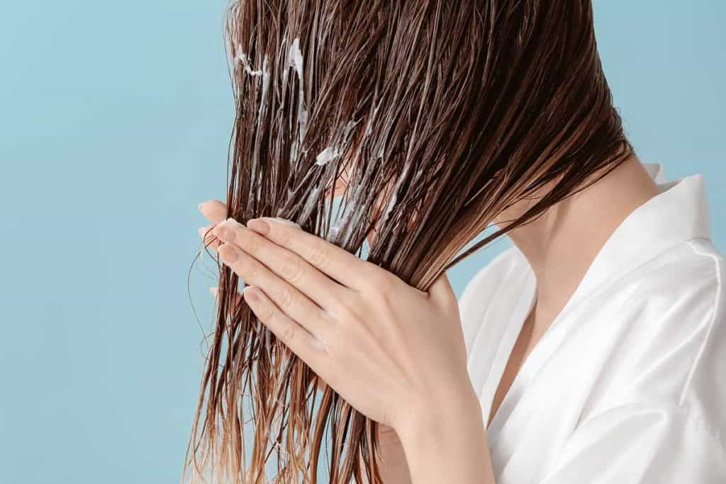 A beautiful young woman applying mousse on her hair after washing, How To Get Mousse Out Of Your Hair