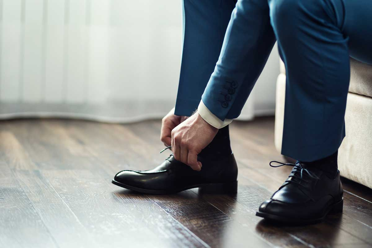 A businessman in suit tying his black leather shoes, What Color Of Shoes Should You Wear With A Blue Suit?
