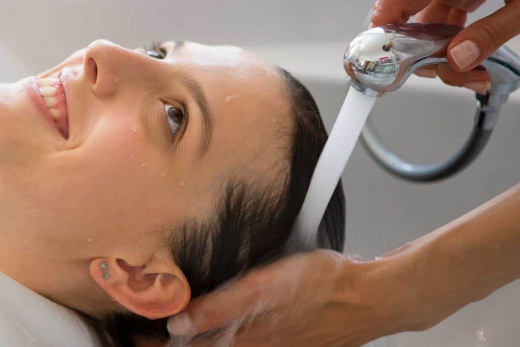 A hairdresser washing hair of a salon customer, Do You Have To Wash Out Hair Mousse?
