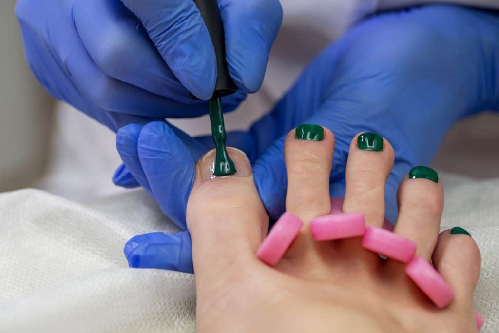 A pedicure expert putting green gel pedicure on her clients nails, How Much Does A Gel Pedicure Cost?