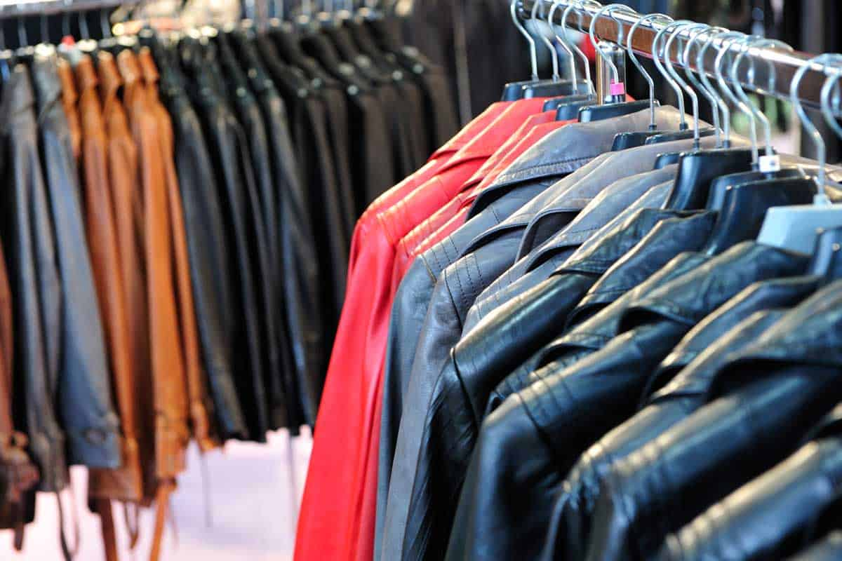 A row of colorful leather jackets hanging on hangers in retail shop, Should You Dry Clean A Leather Jacket?
